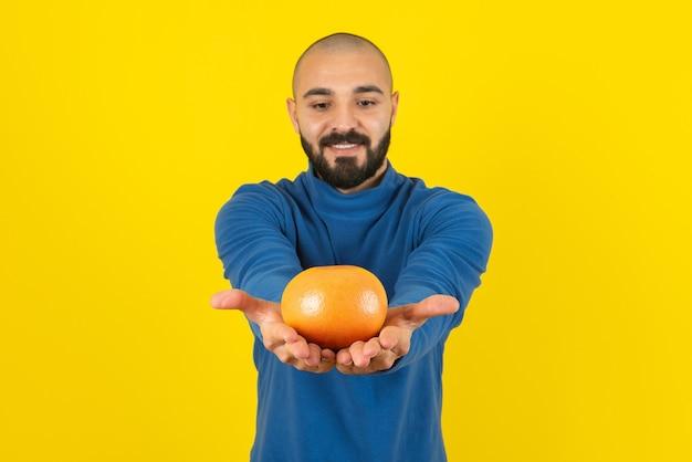 Foto de um modelo de homem mostrando uma fruta laranja contra uma parede amarela.