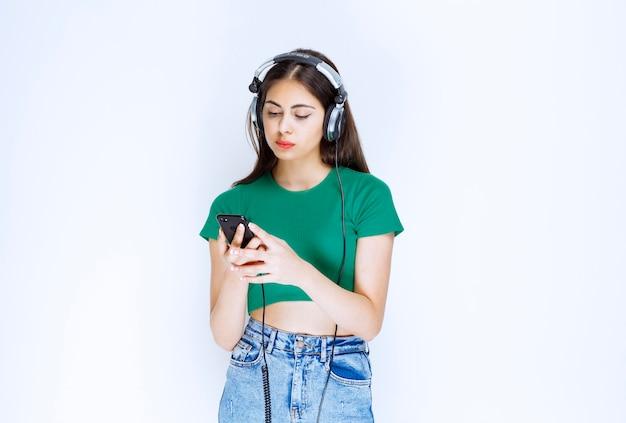 Foto de um modelo de menina bonita com fones de ouvido, usando telefone celular.