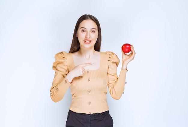 Foto de um modelo de mulher bonita em pé e apontando para uma maçã vermelha fresca.