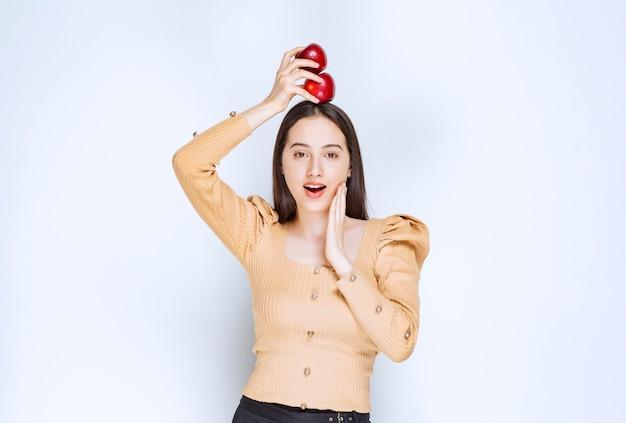 Foto de um modelo de mulher bonita em pé e segurando maçãs vermelhas frescas.