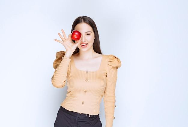 Foto de um modelo de mulher bonita em pé e segurando uma maçã vermelha fresca.