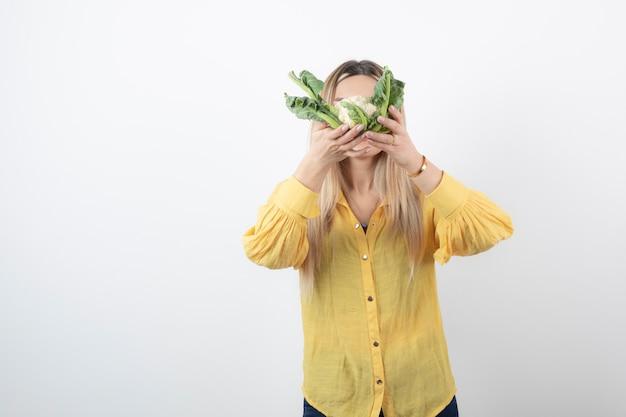 Foto de um modelo de mulher jovem e bonita de pé e cobrindo o rosto com couve-flor.