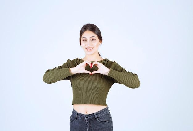 Foto de um modelo de mulher jovem e bonita fazendo a forma do símbolo do coração com as mãos.