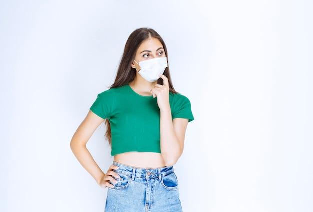 Foto de um modelo de mulher jovem em pé e usando máscara médica protetora.