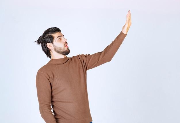 Foto de um modelo jovem atraente em pé e levantando a mão. foto de alta qualidade
