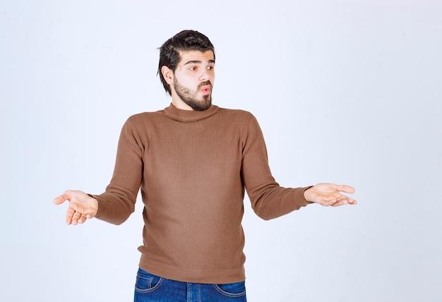 Foto de um modelo jovem surpreso em pé com as mãos levantadas e desviar o olhar. foto de alta qualidade