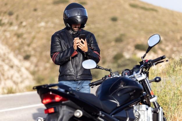 Foto de um motociclista falando ao telefone com o seguro de sua motocicleta após ter sofrido uma pane na estrada.