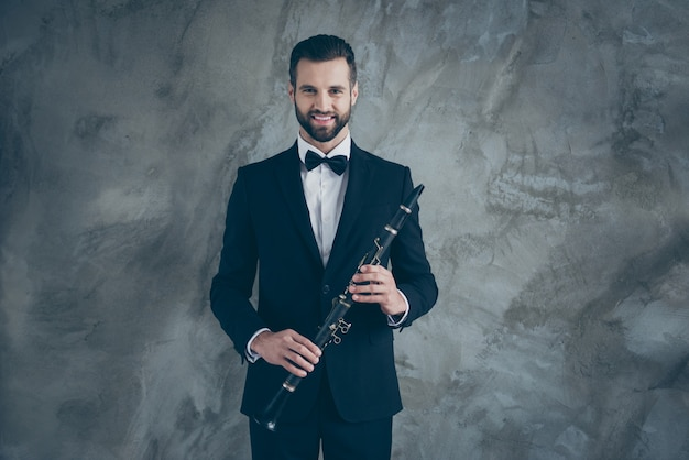 Foto de um músico profissional alegre e divertido, segurando um clarinete antes de tocar a parede de concreto de cor cinza isolada com dentes sorrindo