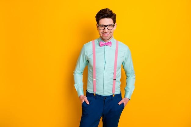 Foto de um namorado bonito com roupas legais em pé, com autoconfiança, mãos nos bolsos, sorrindo, usando especificações, camisa, suspensórios, calças, gravata borboleta, fundo amarelo