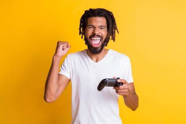 Foto de um negro maluco segurando joystick, joystick, boca aberta, levantar, braço, punho, usar camiseta branca com fundo de cor amarela isolada