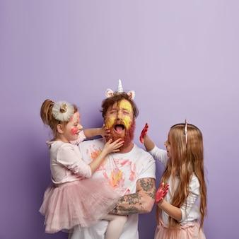 Foto de um pai chateado e cansado sendo manchado com aquarelas por crianças que deixam marcas de palmas em seu rosto