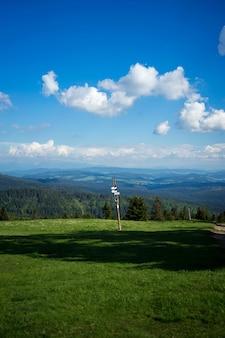 Foto de um poste de sinalização contra uma paisagem de árvores e colinas