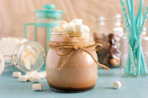 Foto de um pote de cacau. top em uma bebida quente é um slide de marshmallow.