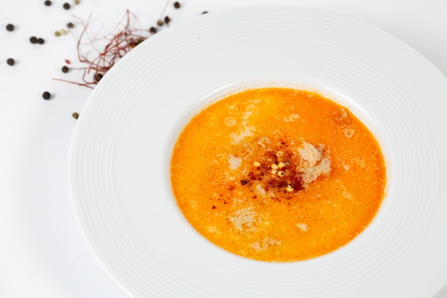 Foto de um prato de sopa com sopa tripla em uma mesa branca decorada com bolas de pimenta preta