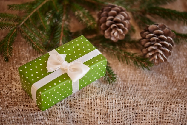 Foto de um presente de natal embrulhado e pinhas