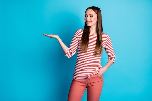 Foto de um promotor positivo de menina alegre segurar a mão, apresentar, olhar, anúncios, promoção, usar roupas casuais, isoladas, sobre, azul, cor, fundo