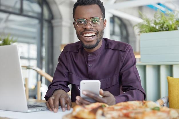 Foto de um próspero gerente de escritório de pele escura usa celular moderno para enviar mensagens, funciona em um laptop portátil