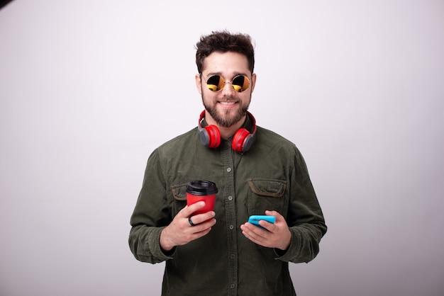 Foto de um rapaz bonito com óculos escuros e fones de ouvido, segurando uma xícara e um smartphone