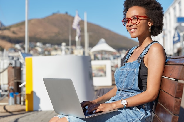 Foto de um redator satisfeito ou de keyborads freelancer com informações no teclado do laptop, pensa em algo criativo, usa roupas casuais, modelos em bancada ao ar livre, trabalha como freelance, usa 4g