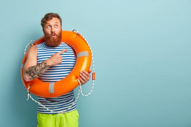 Foto de um salvador de cabelos vermelhos surpreso e perplexo com uma bóia salva-vidas