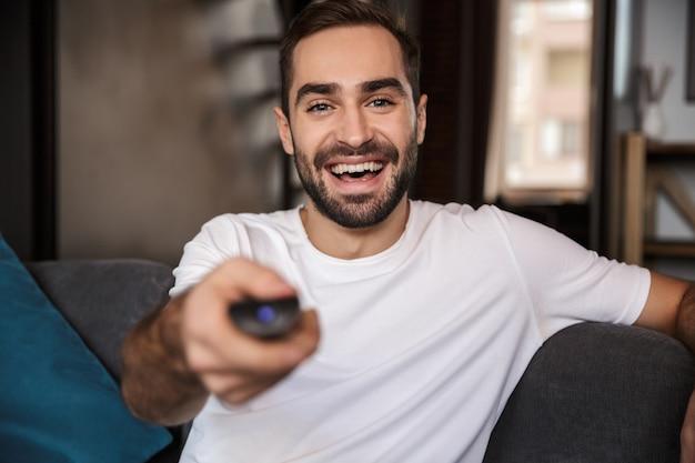 Foto de um solteirão alegre dos 30 anos vestindo uma camiseta casual segurando o controle remoto enquanto está sentado no sofá na sala de estar