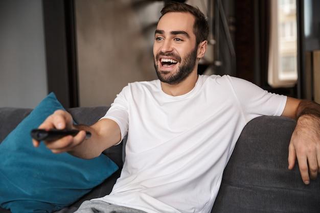 Foto de um solteiro europeu dos anos 30 vestindo uma camiseta casual segurando o controle remoto enquanto está sentado no sofá na sala de estar