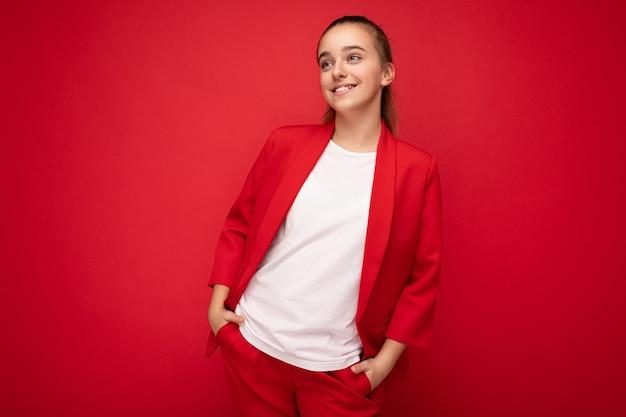 Foto de um sorriso positivo e encantador da pequena adolescente feminina, morena, vestindo uma jaqueta vermelha da moda e uma camiseta branca para maquete em pé isolado