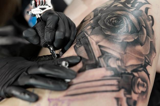 Foto de um tatuador barbudo fazendo uma tatuagem na perna de uma mulher
