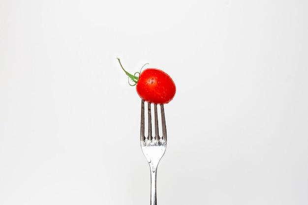 Foto de um tomate cereja fresco em um garfo isolado em um fundo branco