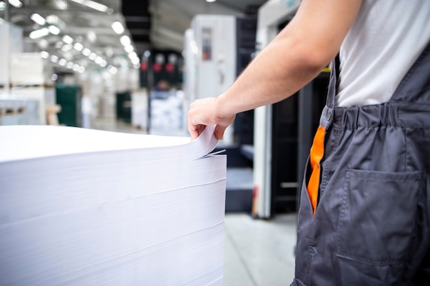 Foto de um trabalhador de impressão pronto para colocar folhas de papel em branco na máquina offset para impressão