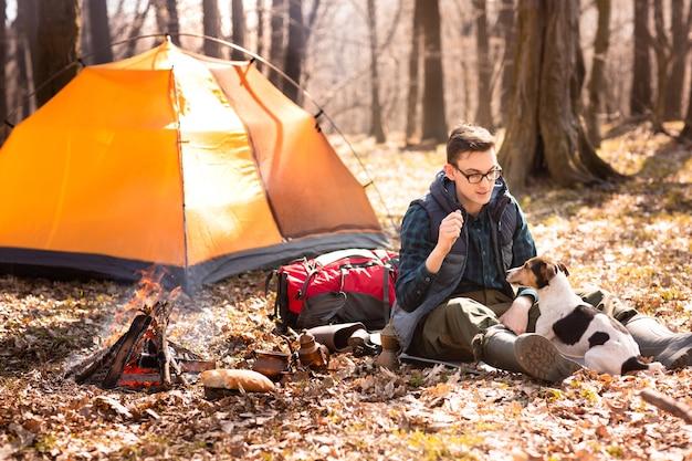 Foto de um turista com um cachorro, descansando na floresta perto do fogo e tenda laranja
