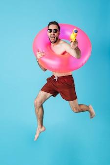 Foto de um turista europeu sem camisa usando um anel de borracha e sorrindo enquanto brincava com um brinquedo de arma de água isolado