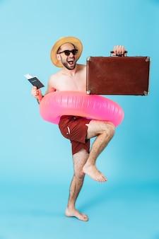 Foto de um turista europeu sem camisa usando um anel de borracha segurando passagens com passaporte e carregando bagagem isolada