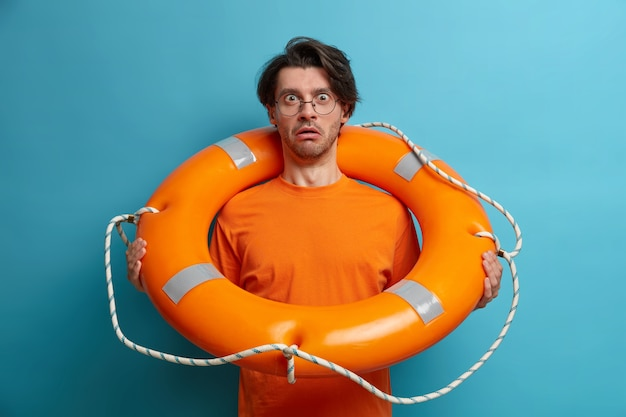Foto de um turista homem surpreso fica dentro de uma boia salva-vidas inflada, indo nadar no mar, goza de férias na praia de segurança, vestido casualmente, isolado na parede azul. resgate na água. estilo de vida de viagens