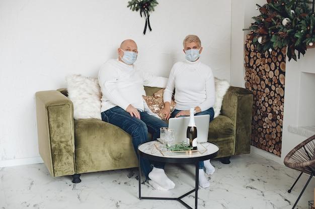 Foto de um velho casal apaixonado por máscaras médicas passando o natal juntos