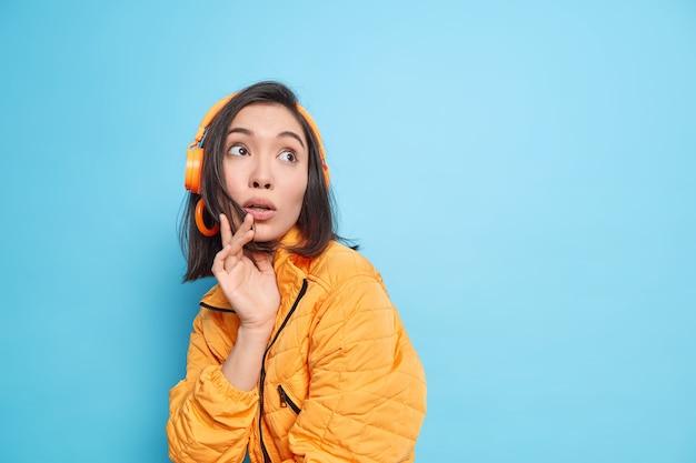 Foto de uma adolescente asiática fascinada e surpresa focada com uma expressão de medo e choque acima, vestida com uma jaqueta laranja, ouve música da lista de reprodução por meio de fones de ouvido isolados sobre a parede azul