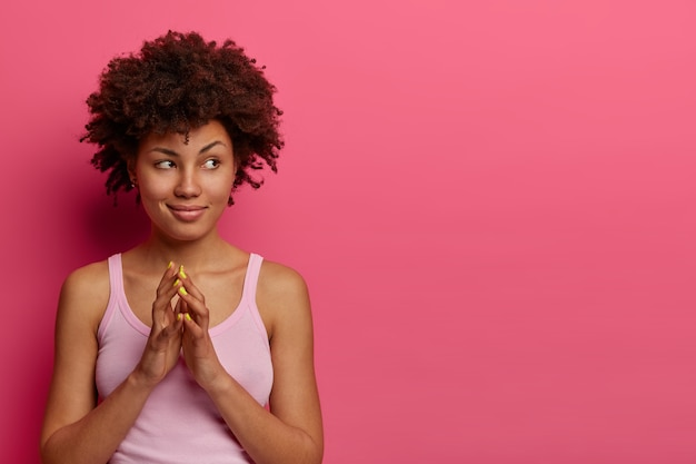Foto de uma adolescente encaracolada astuta com dedos curvados, esquematiza algo, inventou uma boa ideia, pondera sobre algo, parece misteriosamente de lado, usa uma camisa casual, posa dentro de uma parede rosada