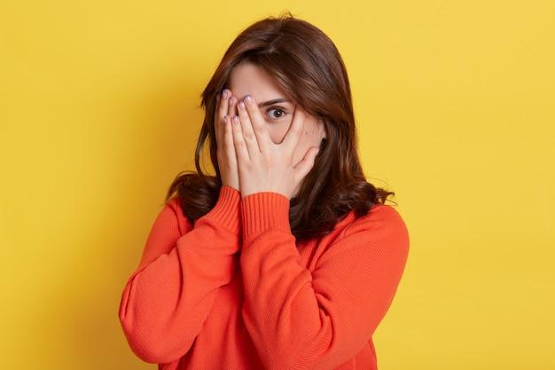 Foto de uma adolescente morena tímida cobrindo o rosto com as mãos e espiando por entre os dedos. jovem mulher atraente, escondendo o rosto, estando assustada, assustada ou envergonhada, usa casualmente.
