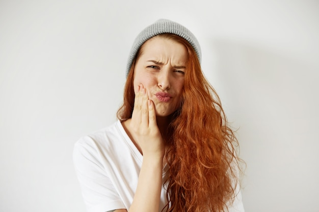 Foto de uma adolescente ruiva pressionando sua bochecha com expressão de dor