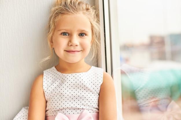 Foto de uma adorável menina pré-escolar com grandes olhos azuis usando um lindo vestido com um sorriso feliz e animado, procurando amigos em sua festa de aniversário, sentada perto da janela
