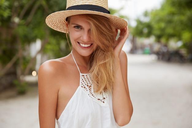 Foto de uma adorável modelo feminina que usa vestido branco e chapéu de palha de verão, caminha ao ar livre, tem um clima quente e brilhante, tem a pele bronzeada, dentes perfeitos