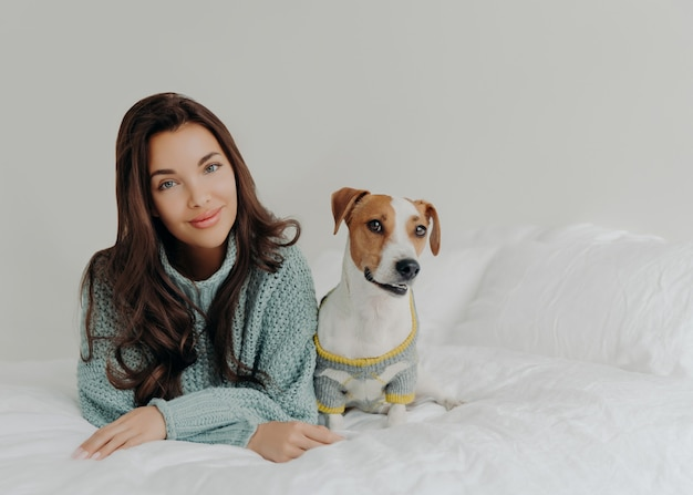 Foto de uma adorável mulher de cabelos escuros vestindo seu cachorro para o tempo frio, indo para uma caminhada ao ar livre, deitados juntos em uma cama confortável
