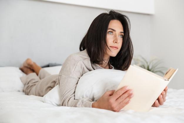 Foto de uma adorável mulher dos anos 30 lendo um livro, deitada na cama com lençóis brancos em casa