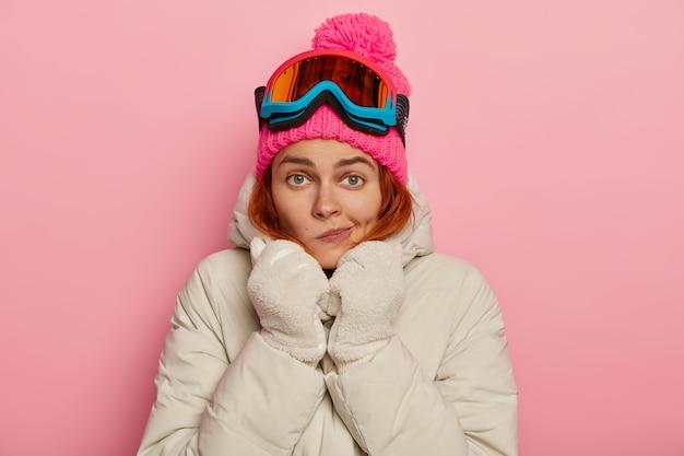 Foto de uma adorável mulher viajante franzindo os lábios, se aquecendo em roupas confortáveis durante o inverno, usando máscara de esqui