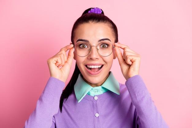 Foto de uma adorável senhora com a câmera tirando os óculos, a boca aberta, animada, especificações de desgaste, cardigan violeta, fundo cor-de-rosa isolado