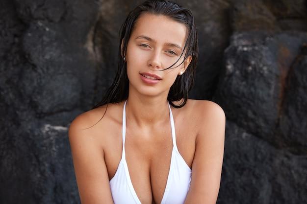 Foto de uma agradável mulher caucasiana sendo molhada depois de nadar no mar