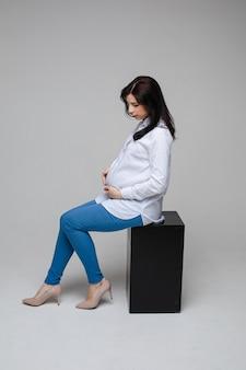 Foto de uma alegre mulher grávida com cabelo preto e um lindo sorriso em uma camisa branca e calça jeans, sentada em uma cadeira e posando para a câmera