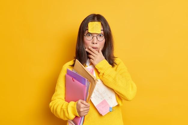 Foto de uma aluna asiática surpresa e intrigada com um memorando preso na testa prepara o trabalho do curso carrega pastas com papéis faz o projeto educacional funcionar em sua tarefa estuda remotamente