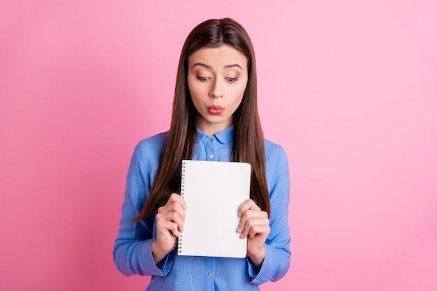 Foto de uma aluna linda e simpática olhando para um pedaço de papel em branco