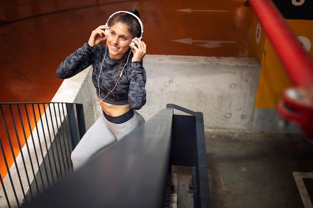 Foto de uma atleta atraente com fones de ouvido, preparando-se para o treinamento de corrida.